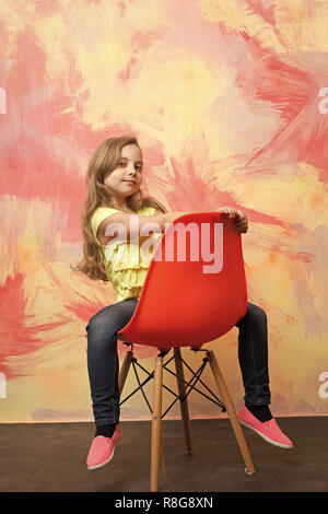 girl. kid or small smiling girl sitting on orange chair on colorful abstract background in jeans and tshirt with long blond hair