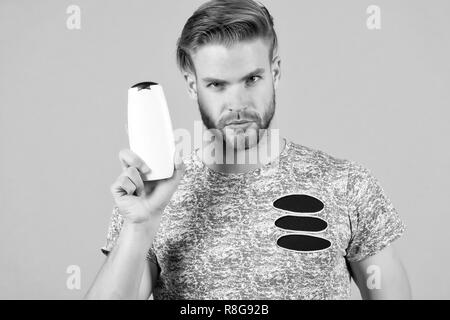 Man enjoy freshness after washing hair with shampoo. Guy with hairstyle holds bottle shampoo, copy space. Hair care and beauty supplies concept. Man strict face holds shampoo bottle, grey background. - Stock Photo