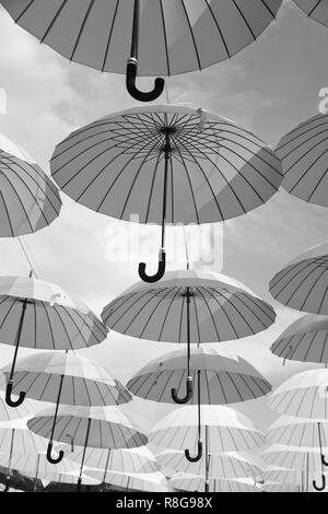 Outdoor art design and decor. Umbrellas float in sky on sunny day. Umbrella sky project installation. Holiday and festival celebration. Shade and protection.