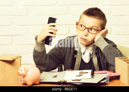 young cute businessboy in grey sweater and glasses sitting at table with papers pink piggy pig bank and holding cell phone on white brick wall background. - Stock Photo