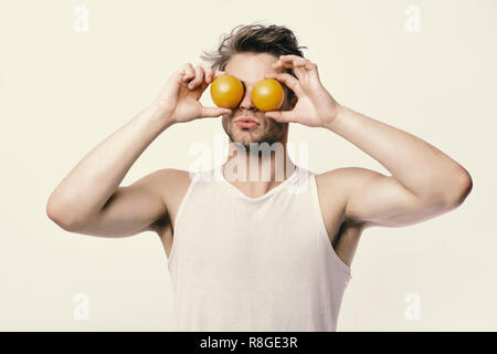 Athlete with messy hair holds fresh fruit. Guy with serious face isolated on light grey background. Man with orange instead of eyes in his hands. Diet and healthy lifestyle concept - Stock Photo