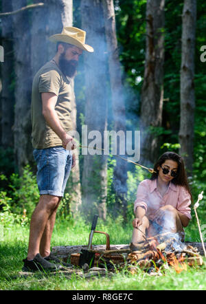 Roasting marshmallows popular group activity around bonfire. Couple in love camping forest roasting marshmallows. Couple friends prepare roasted marshmallows snack nature background. Camping activity. - Stock Photo