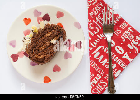 Slice of M&S Yuletide Log on plate with fork on Christmas serviette napkin - from above looking down on - Stock Photo
