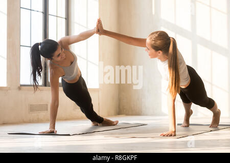 Girls doing side plank and holding hands - Stock Photo