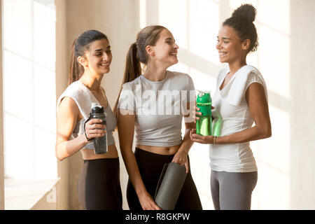 Happy friends talking after yoga session at gym - Stock Photo