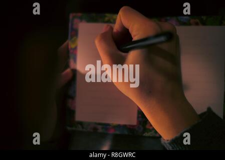 A young girl writes a Christmas Gift list - Stock Photo