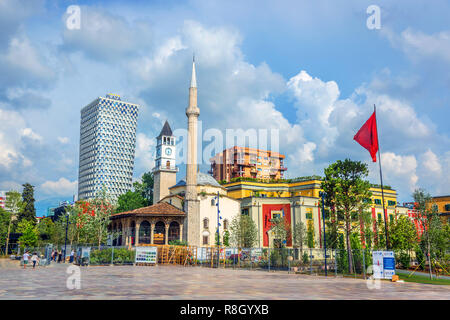 Tirana, Albania - June 2nd 2018 - The downtown city of Tirana with the Plaza hotel in the background, a mosque and the Albania flag in a summer day - Stock Photo