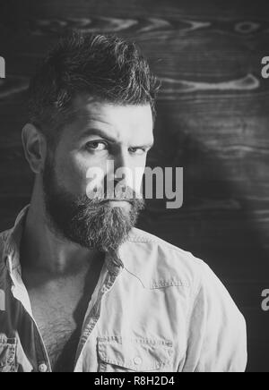 Barber and hairdresser salon. Man with beard and mustache on wooden background. Haircut of bearded man, archaism. Serious hipster in barbershop, look. Fashion and male beauty of graying man. - Stock Photo