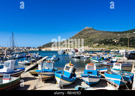 View of Favignana harbor full of traditional fishing boats with Forte Santa Caterina in the background, Aegadian Islands, Sicily, Italy - Stock Photo