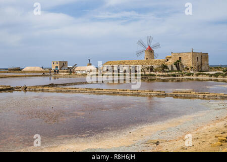 Landscape with saline and windmill at Saline di Trapani e Paceco nature reserve, Sicily, Italy - Stock Photo