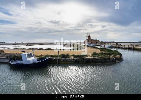 "Traditional fishing boat near Salt Museum windmill at ""Saline dello Stagnone"", Marsala, Sicily, Italy - Stock Photo"