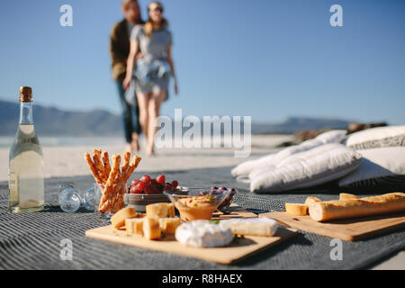 Food and drink on the blanket at the beach with couple walking towards it. Picnic setting on the beach with man and woman in background. - Stock Photo