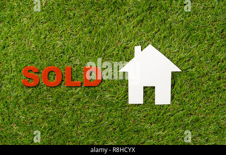 Conceptual picture of paper house and word Sold on green grass field top view and copy space in Property investment business Real estate selling and b - Stock Photo
