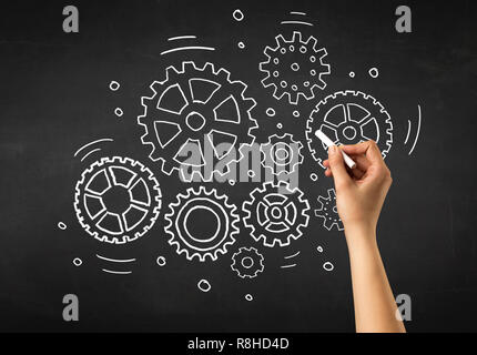 Female hand holding white chalk in front of a blackboard with gears drawn on it - Stock Photo
