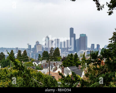 Skyline of Seattle from residential neighborhood on overcast day - Stock Photo