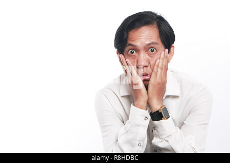Photo image portrait of a funny young Asian businessman wearing glasses looked very bored, close up portrait showing tired face with both hands cheek - Stock Photo