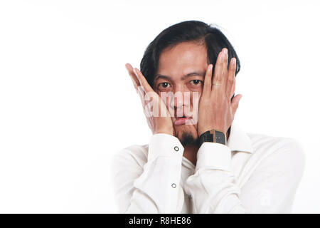 Photo image portrait of a funny young Asian businessman wearing glasses looked very bored, close up portrait showing tired face with both hands pressi - Stock Photo
