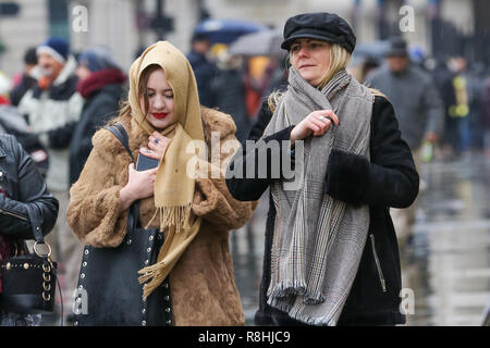 London, UK. 15th December 2018. Couple women wrap-up warm with scarf & winter coat on a cold and wet day in London as snow has fallen in some parts of Britain.   Credit: Dinendra Haria/Alamy Live News - Stock Photo