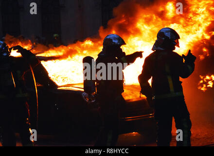 Paris, France. 8th Dec, 2018. Firefighters try to extinguish a fire during the 'Yellow Vest' protest in Paris, France, on Dec. 8, 2018. Credit: Li Genxing/Xinhua/Alamy Live News - Stock Photo