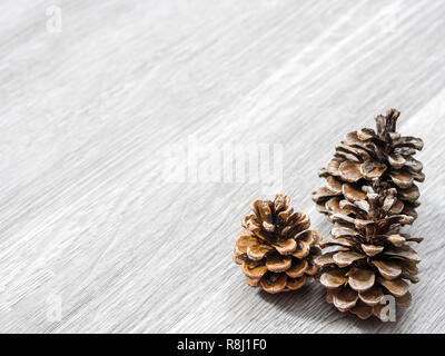 Three brown pine cones laying in the corner of image and isolated on a background of gray wood grain texture flooring making a beautiful winter or Chr - Stock Photo