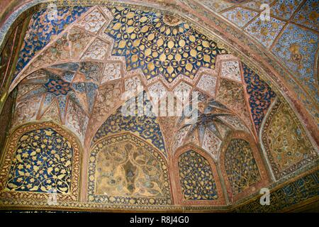 A colourful patterned mosaic domed roof with golden designs in India - Stock Photo