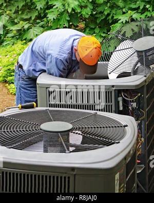 Repairman working on an air conditioner unit at the back of a house - Stock Photo