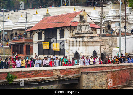 People on a bridge watching a Hindu funeral on the ghat upon the Bagmati River at Sacred Hindu Pashupatinath Temple in Kathmandu, Nepal - Stock Photo
