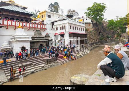 People watching a Hindu funeral on the ghat upon the Bagmati River at Sacred Hindu Pashupatinath Temple in Kathmandu, Nepal - Stock Photo