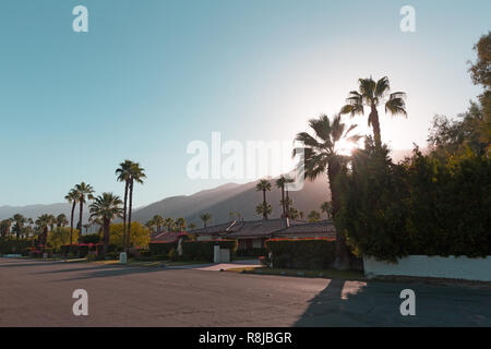 The sun goes behind the mountains before the dusk in Palm Springs, California, USA. A stream of sunlight on the mountains surrounding Palm Springs tow - Stock Photo