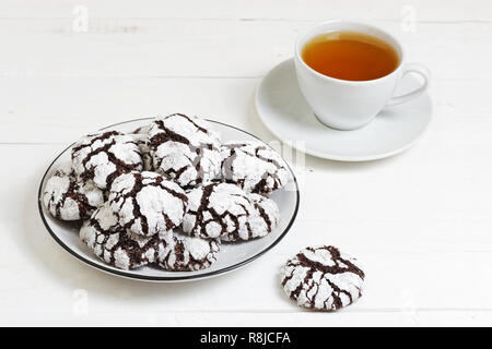 Homemade chocolate crinkles cookies powdered sugar and cup of tea on white wooden table. - Stock Photo