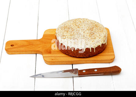 Homemade sweet carrot cake with walnuts, cinnamon and white icing on white wooden table - Stock Photo
