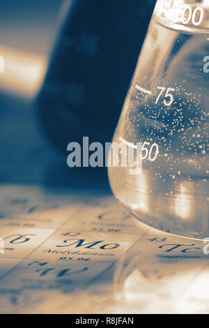 Chemicals in glass laboratory flask on the periodic table chart with colour toning - Stock Photo
