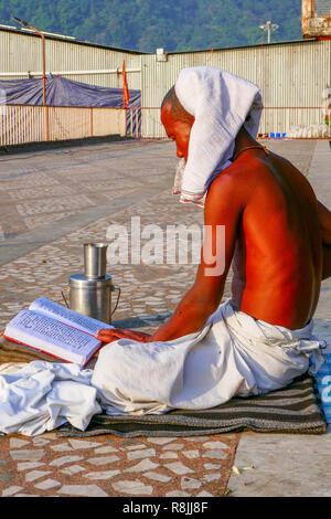 yogi sitting on the pavement and reading in Rishikesh, India - Stock Photo