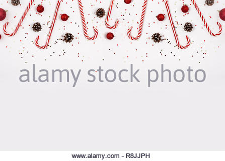 Christmas border made with candy cane, red balls and cones on white background. View from the top. - Stock Photo