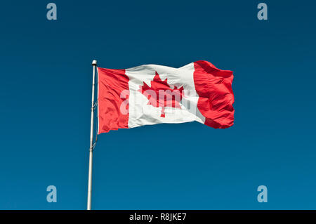 Canadian Flag on a flagpole waving in the breeze - Stock Photo