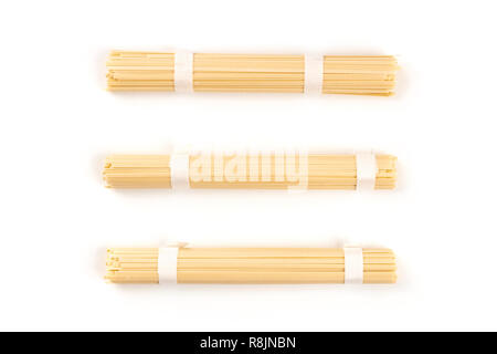 Three individually wrapped portions of udon noodles, shot from the top on a white background with a place for text - Stock Photo