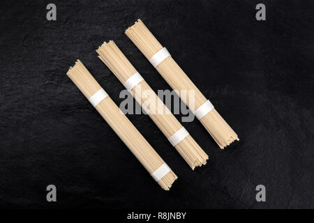 A photo of three individually wrapped portions of udon noodles, shot from the top on a black background with a place for text - Stock Photo