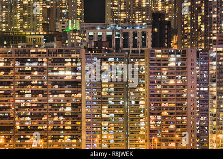 Densely populated skyscraper living towers of houses in Hong Kong at night with bright illumination of windows on island's waterfront.