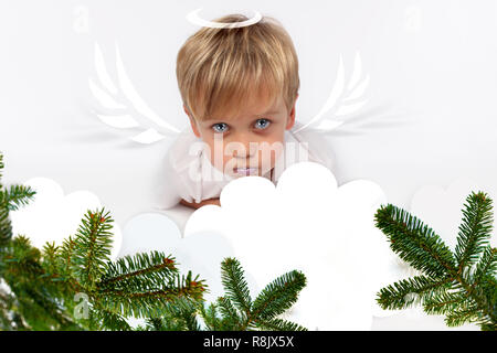 Naughty or good child for Christmas card? PF or letter to Santa-Claus for Christmas. Little child boy appearing as an adorable angelic devil - Stock Photo