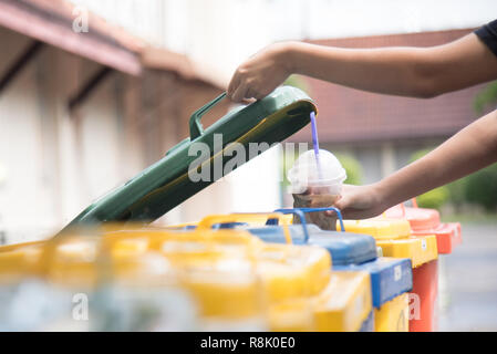 children hand throwing empty plastic bottle into the trash.saving environment by throwing plastic jung in to the recycle bin or garbage - Stock Photo