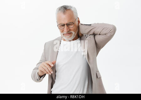 Man feeling pain in spine after hardworking sitting for long time. Portrait of displeased bothered mature male with white beard and hair in glasses touching back of neck complaining on pain - Stock Photo