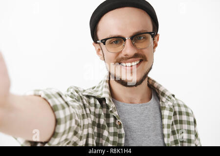 Close-up shot of friendly handsome neat guy in black trendy beanie and glasses with moustache smiling broadly pulling hand to hold camera while taking selfie on brand new smartphone - Stock Photo
