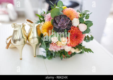 bright wedding bouquet of summer dahlias and roses with women high-heeled shoes - Stock Photo