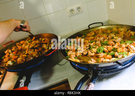 Two paella pan preparing the chicken and the fried vegetables. - Stock Photo