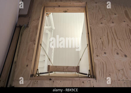 Wooden staircase to the attic in a modern house empty - Stock Photo