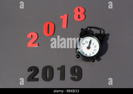 2018, 2019 and black vintage alarm clock on gray background - Stock Photo