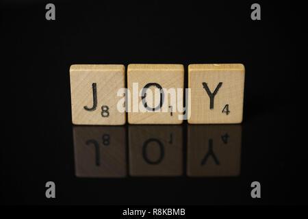 WOODBRIDGE, NEW JERSEY - November 9, 2018: Scrabble tiles spell out the word joy on a reflective black background - Stock Photo