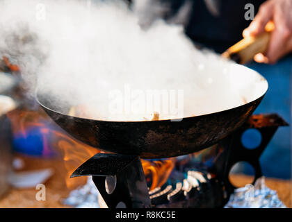 Stirring Food in the wok in the street food market on the background. - Stock Photo