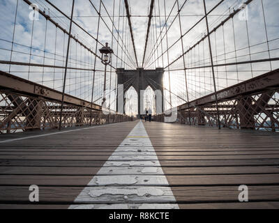 View of Couple Walking on the Brooklyn Suspention Bridge At Sunrise - Stock Photo