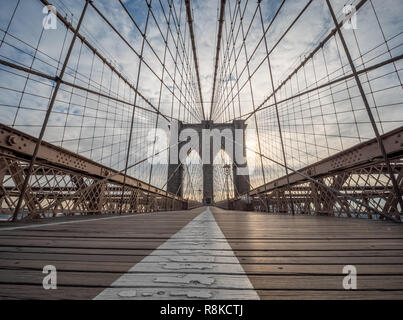 A Low Angle View of the Brooklyn Bridge Upper Walking Deck During Sunrise - Stock Photo